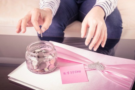 Placing money in a jar labelled wedding on top of a wedding album
