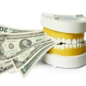 Dental mold biting down on several large note dollar bills