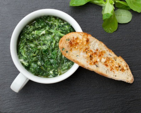 Bowl of garlic sautéed spinach with a piece of bread resting on the edge of the bowl