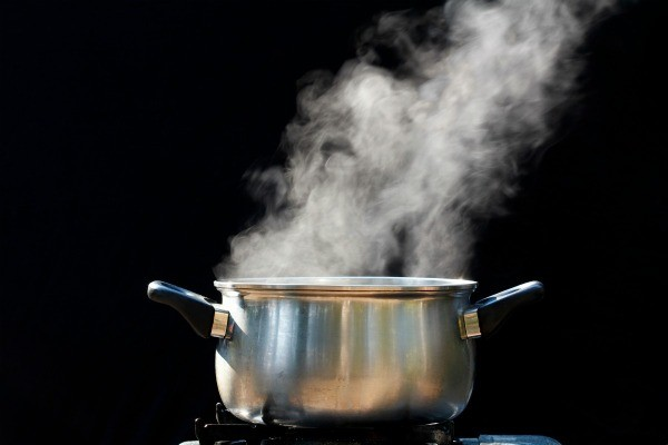 Silver pot with steam coming out of it against black background