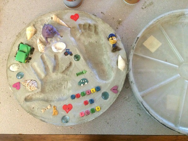 Using Flower Pot Saucers for Stepping Stones - Finished stepping stone with small toys around the hand and foot print.