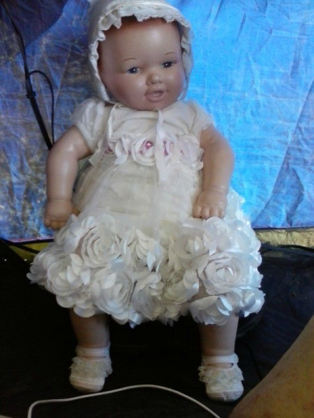 baby doll wearing white dress and bonnet