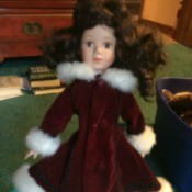 dark haired doll wearing a dark maroon coat with white fur collar and cuffs