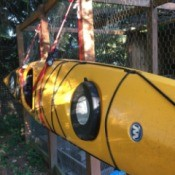 A kayak being hung on the side of a chicken coop.