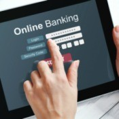 "Hands using a tablet displaying the words ""Online Banking"""