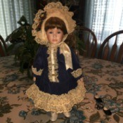 doll wearing blue coat with lace trim and matching hat