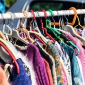 rack of women's sweaters at a flea market