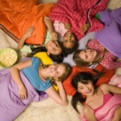 Group of girls in sleeping bags in a circle with heads together