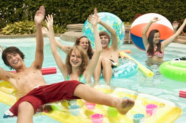 Teenage boys and girls playing in a pool