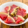 Several slices of pickled watermelon in a white bowl