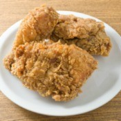 Crispy fried chicken breasts on a white plate