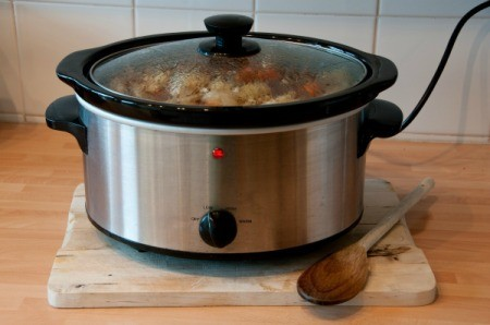 Crockpot plugged in and cooking meal on a wooden counter.