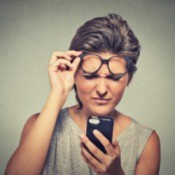 Woman looking at cell phone with confused expression