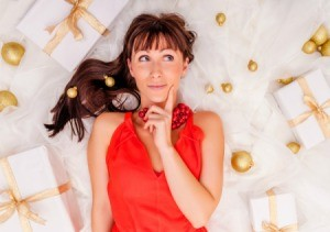 Woman looking thoughtful surrounded by Christmas decorations and gifts