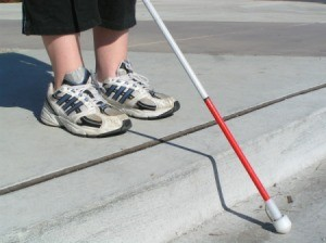 Woman's feet in sneakers near a curb holding a while cane with red marking.