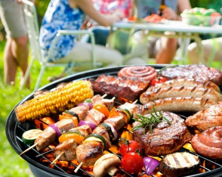 Barbecue grill with a variety of meats, shish kabobs, corn and veggies with a family in the background