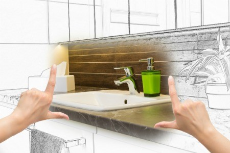 Hands framing renovated bathroom brought to life from a sketch