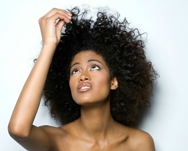African American woman with natural hair holding a strand and looking at it with concern