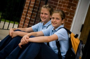 Two girls in private school uniforms sitting on steps in front of brick building