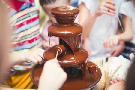 Chocolate fountain with people dipping marshmallows and fruit