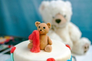 Cake with fondant teddy bear decoration and a teddy bear stuffed toy in the background