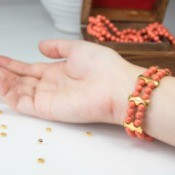 Elastic Beaded Bracelet on a girls wrist near string of matching beads and small gold beads loose on counter