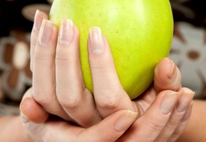 hands with long fingernails holding an apple