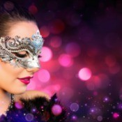 Woman in masquerade mask against sparkly background