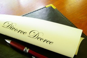 Rolled up divorce decree with pen on legal pad