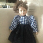 doll wearing a dress with blue and white checkered top and dark skirt