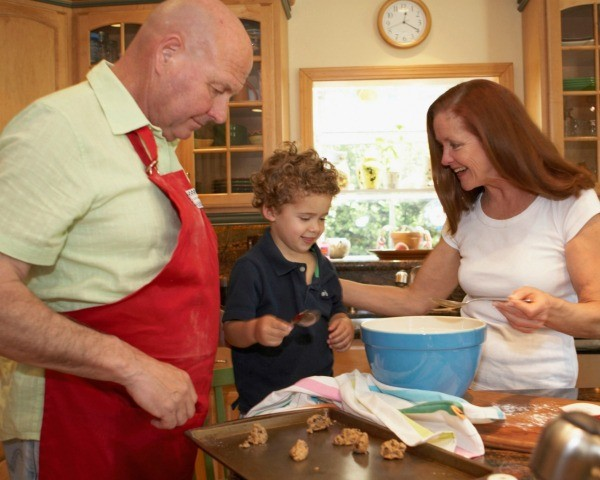 Child baking cookies with his grandparents