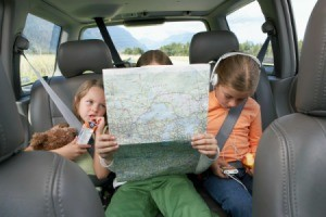 Three girls sitting the back seat of a car.  One is holding a map.