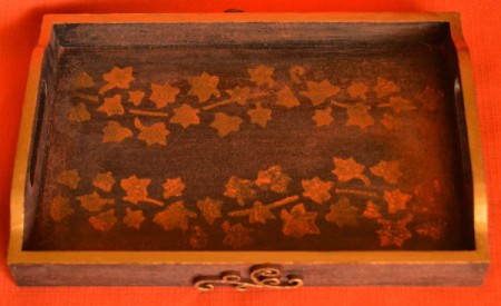 "A tray with a stamped ""inlay"" of leaves."