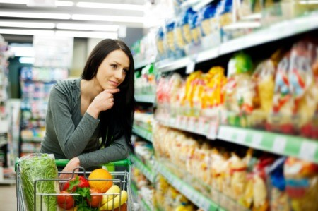Woman leaning on her cart thoughtfully at the grocery store