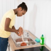 Woman using a plunger on a kitchen sink