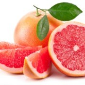 A cut up grapefruit and a whole grapefruit.