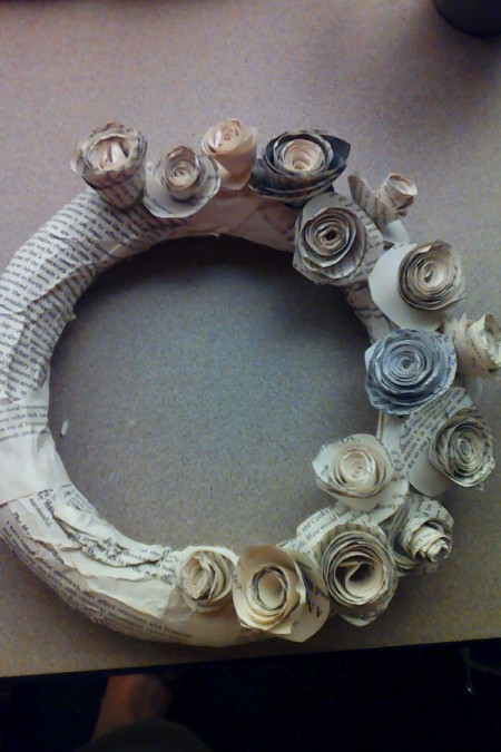 A wreath form with rosettes being added to one side.