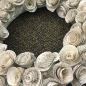 A closeup of a wreath made from paper rosettes.