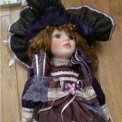 doll wearing purple dress with lace