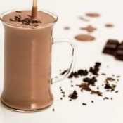 Glass of chocolate beverage with shaved chocolate and chocolate bar in the background
