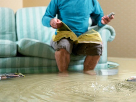 Man sitting on couch looking through phone book in flooded room with water up past his ankles