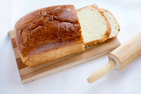Loaf of bread with rolling pin on white background