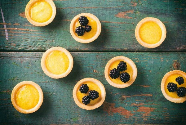 Several lemon curd tarts on a antiqued painted table
