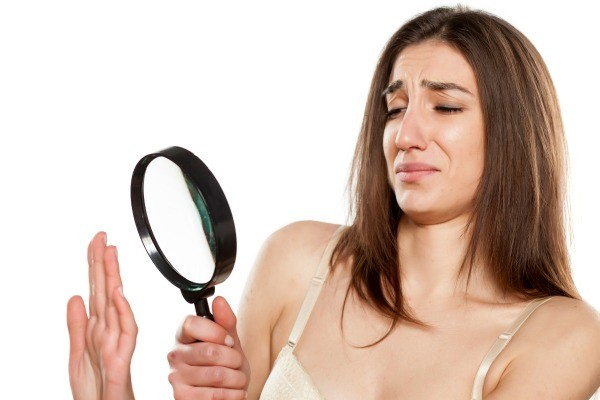 Woman looking at nails through a magnifying glass with distaste