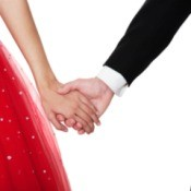 Close up of couple holding hands. Boy is in suit, girl is in a red sparkly party dress