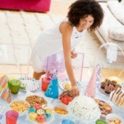 Overhead view of a woman setting up a birthday party table with bright colors candy, treats, and cake