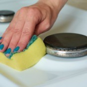Woman's hand cleaning an enamel cooktop