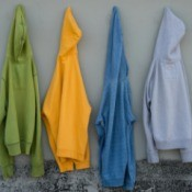 Four old sweatshirts hanging on a wall