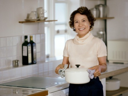 Woman standing in kitchen holding out a casserole dish