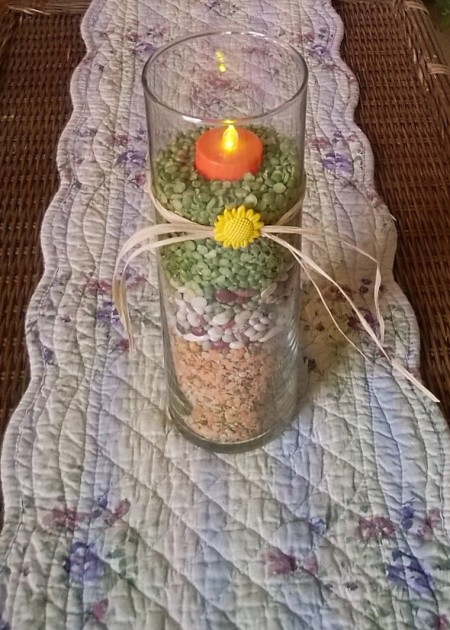 Candle vase filled with dried beans and peas.